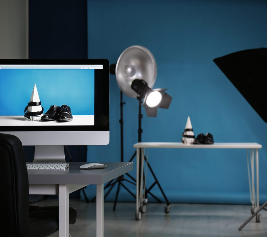 Shooting of men's shoes and belt for product promotion in photo studio, focus on PC screen